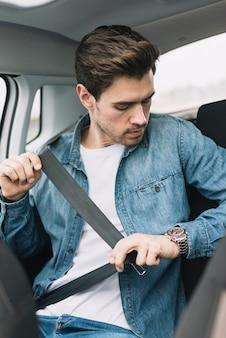 Il giovane che si siede nell'automobile fissa la cintura di sicurezza