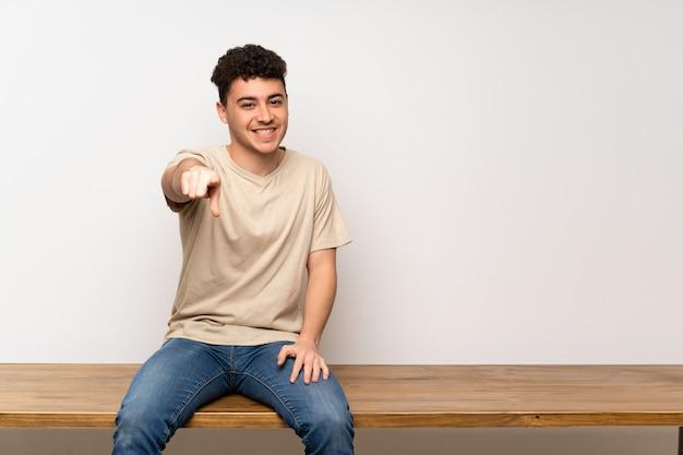 Il giovane che si siede sulla tabella indica il dito con un'espressione sicura