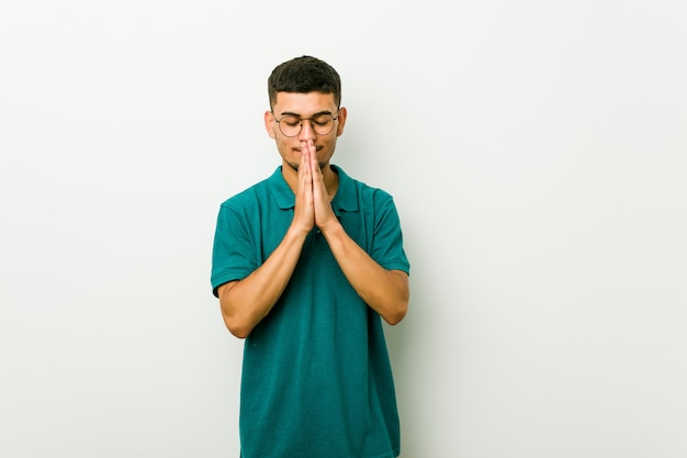 Il giovane che si tiene per mano dentro prega vicino alla bocca, si sente sicuro
