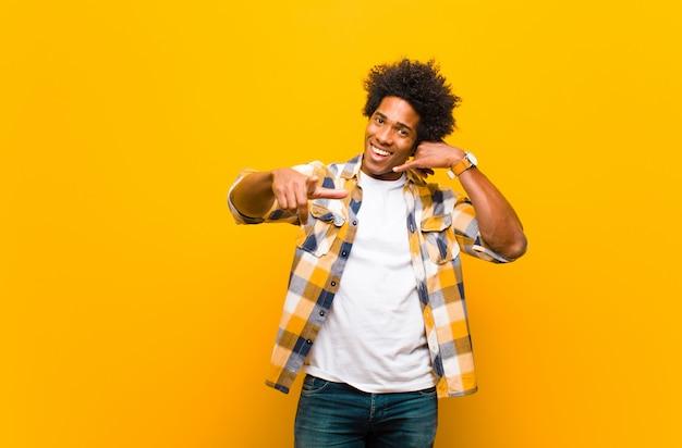 Il giovane che sorride allegramente e che indica la macchina fotografica mentre fa una chiamata più tardi gesticola, parla sul telefono sopra la parete arancio