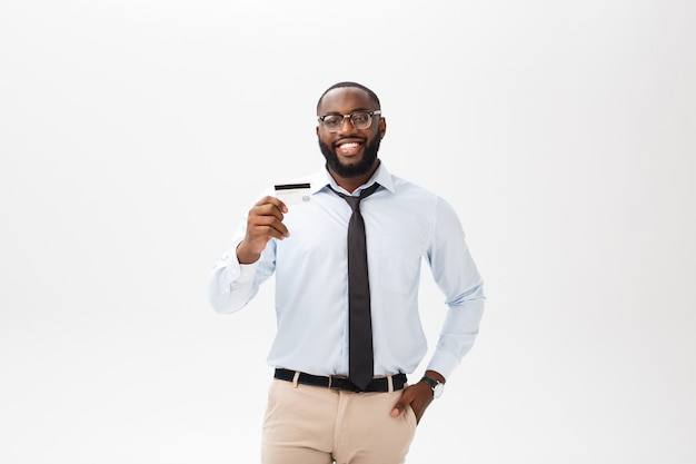 Il giovane che sta in camicia mostra la carta di credito, esamina sorridere della macchina fotografica.