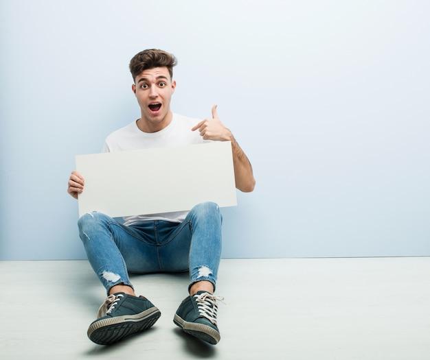 Il giovane che tiene un cartello che si siede sul suo pavimento domestico ha sorpreso indicare se stesso, sorridente ampiamente.