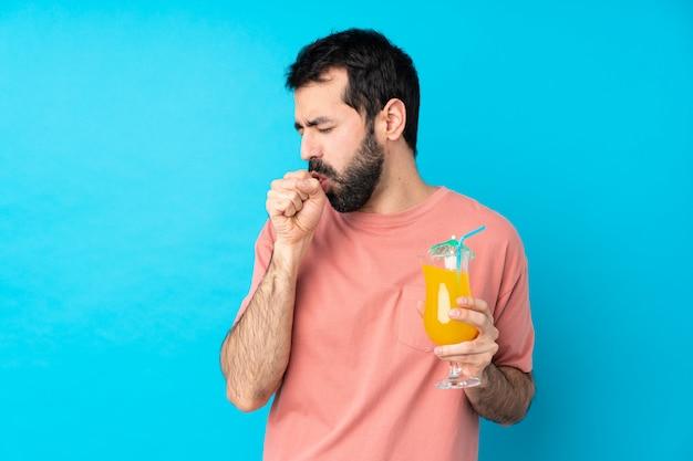 Il giovane che tiene un cocktail sopra la parete blu isolata sta soffrendo di tosse e si sente male