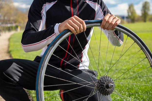 Il giovane ciclista maschio freddo in abiti sportivi e casco protettivo che ripara la camera d'aria della bici spinge dentro il parco