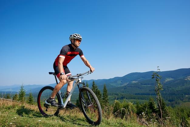 Il giovane ciclista turistico atletico che guida la bici giù la collina erbosa sulle montagne distanti e sul fondo blu del cielo dell'estate. stile di vita attivo e concetto di sport estremo.