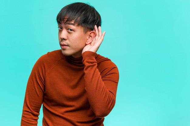 Il giovane cinese prova ad ascoltare un gossip