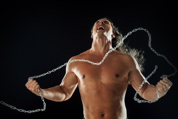 Il giovane con i capelli lunghi rompe la catena di ferro.