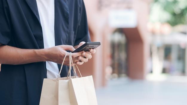 Il giovane con i sacchetti della spesa sta usando un telefono cellulare mentre faceva la spesa
