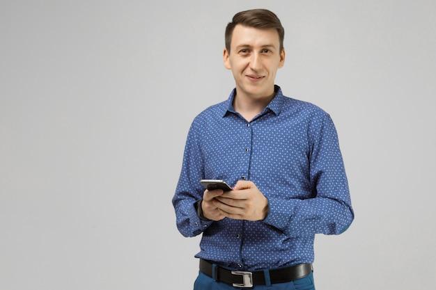 Il giovane con il telefono cellulare in sue mani è isolato su luce