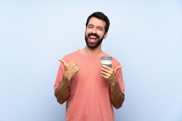 Il giovane con la barba che tiene un caffè asportabile sopra la parete blu isolata con i pollici aumenta il gesto e sorridere