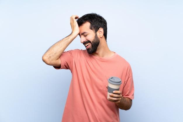 Il giovane con la barba che tiene un caffè da asporto sopra il blu isolato ha realizzato qualcosa e intendendo la soluzione