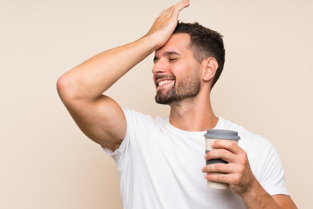 Il giovane con la barba che tiene un caffè da asporto sopra la parete blu isolata ha realizzato qualcosa e intendendo la soluzione