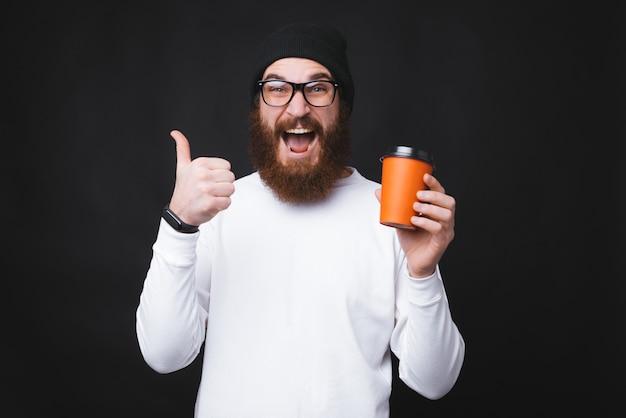 Il giovane con la barba sta mostrando è uscito un pollice in su e in possesso di una tazza con acqua zappa.