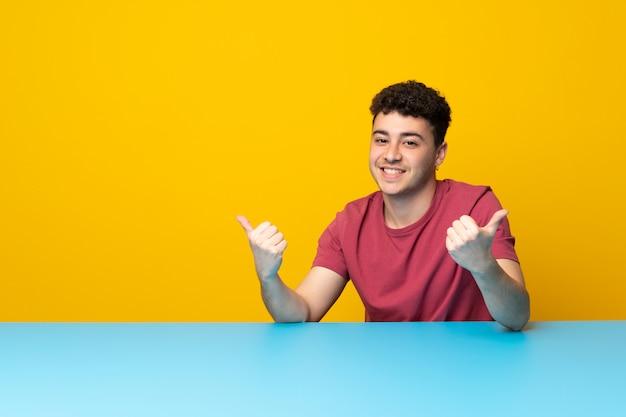 Il giovane con la parete variopinta e la tavola con i pollici aumentano il gesto e sorridere