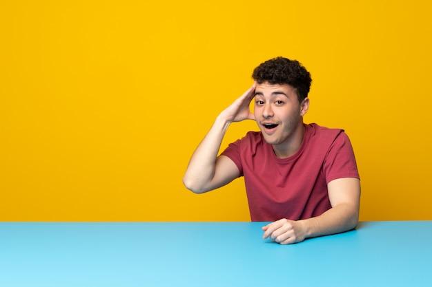Il giovane con parete e tavolo colorati ha appena realizzato qualcosa e ha intenzione di risolverlo