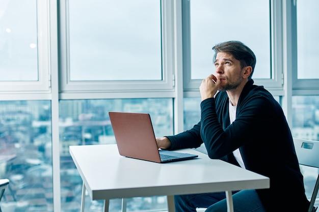 Il giovane con un computer portatile funziona e si riposa