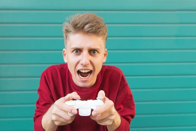 Il giovane con un gamepad in mano gioca ai videogiochi sulla parete turchese.