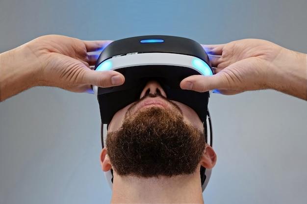 Il giovane con una barba esamina gli occhiali 3d sui precedenti blu