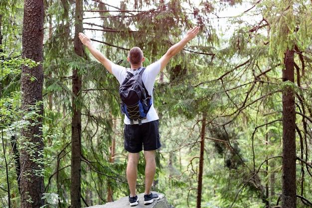 Il giovane con uno zaino che sta le mani su su una roccia nella foresta di conifere