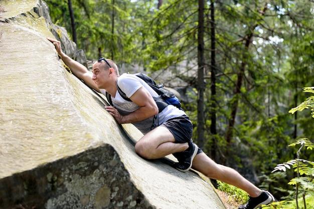 Il giovane con uno zaino scala la scogliera nella foresta di conifere