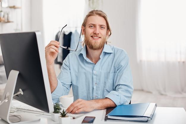 Il giovane copywriter maschio biondo bello barbuto allegro digita le informazioni per la pubblicità sul sito web, indossa la camicia blu e gli occhiali, si siede all'ufficio di coworking davanti allo schermo.