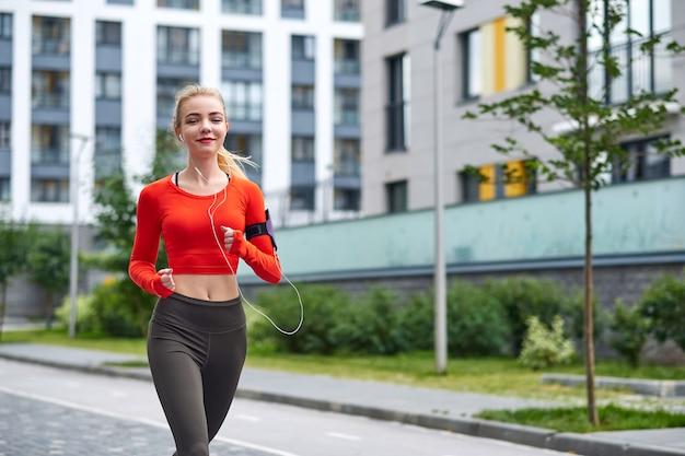 Il giovane corridore femminile in felpa con cappuccio sta facendo jogging nella via della città