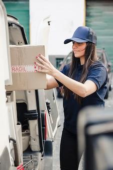 Il giovane corriere femminile ha scaricato la scatola di cartone dal veicolo