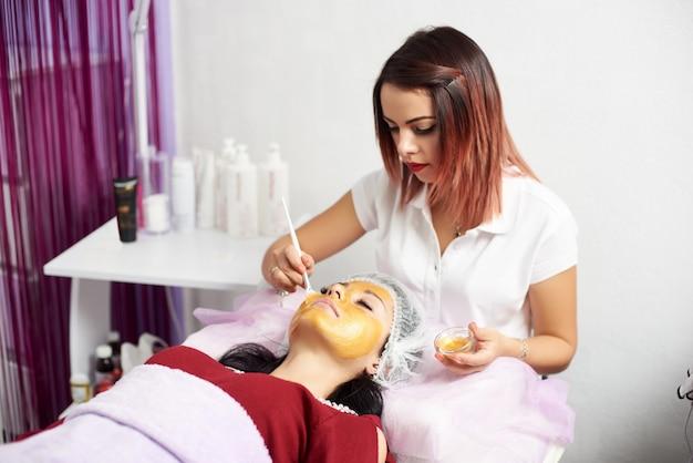 Il giovane cosmetologo sta applicando la maschera d'oro su una faccia di una cliente bruna in un moderno salone di bellezza.