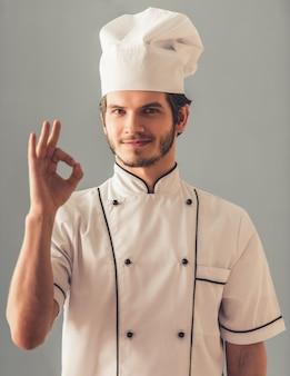 Il giovane cuoco bello in uniforme sta mostrando il segno giusto.