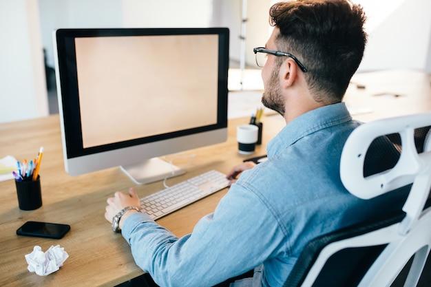 Il giovane dai capelli scuri sta lavorando con un computer sul suo desktop in ufficio. indossa la camicia blu e sembra occupato. vista dal retro.