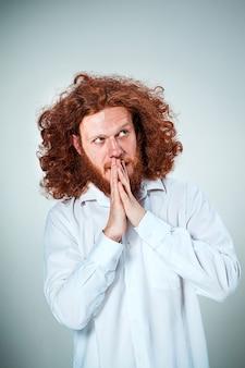 Il giovane dai lunghi capelli rossi che guarda da parte nel pensiero