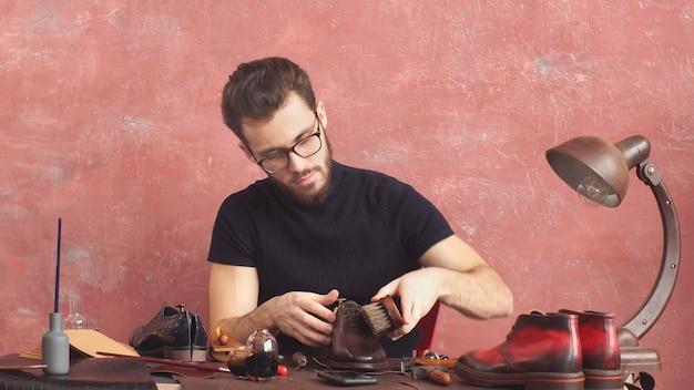 Il giovane designer pulisce gli stivali di pelle seduti su una sedia