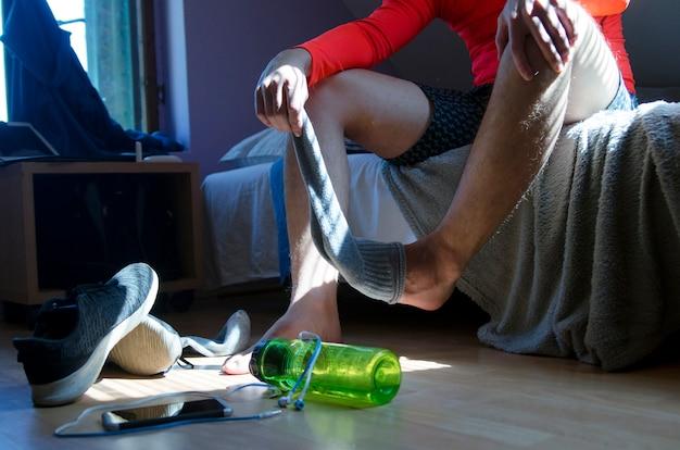 Il giovane dopo l'esercizio fisico prende i suoi calzini nella sua stanza durante la quarantena di coronavirus