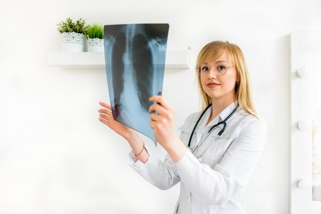 Il giovane dottore cancellerà l'istantanea dei polmoni. diagnosi di tubercolosi polmonare. esame radiografico del paziente.