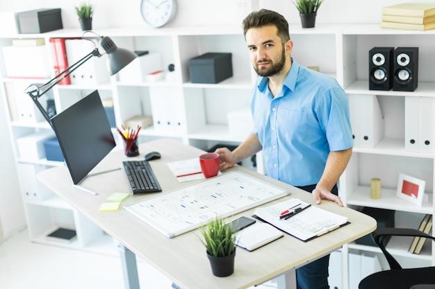 Il giovane è in ufficio al tavolo del computer, beve caffè e lavora con una lavagna magnetica.