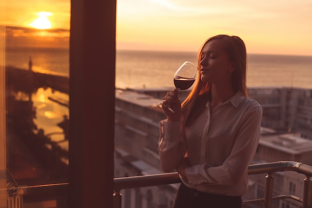 Il giovane è rilassante e bere un bicchiere di vino rosso sul balcone al tramonto la sera