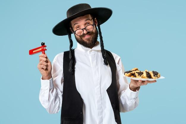 Il giovane ebreo ortodosso con biscotti hamantaschen per il festival purim. vacanza, celebrazione, giudaismo, pasticceria, tradizione, biscotto, concetto di religione