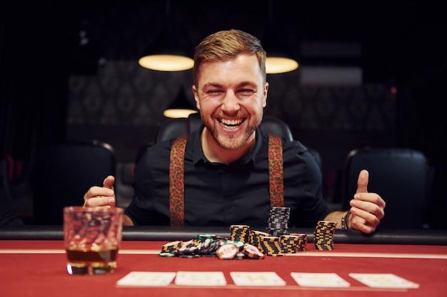 Il giovane elegante felice si siede in casinò e celebra la sua vittoria nel gioco del poker