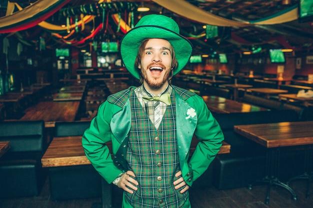 Il giovane emozionante felice si tiene per mano sui fianchi e sorride alla macchina fotografica. indossa l'abito di san patrizio. guy stand alone in pub.
