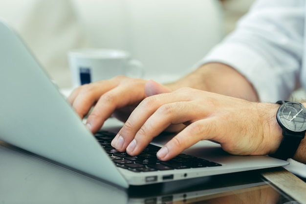 Il giovane esegue il lavoro su un computer portatile