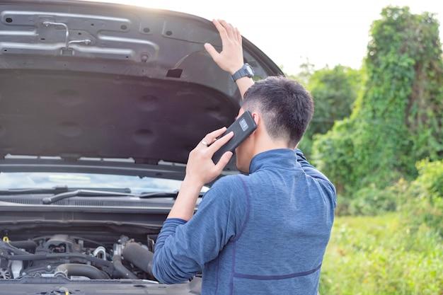 Il giovane fa una telefonata durante l'automobile rotta. l'uomo ha bisogno di aiuto.