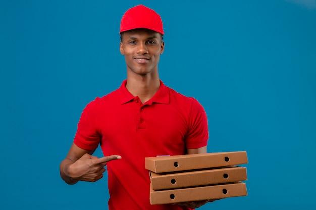 Il giovane fattorino afroamericano che indossa la camicia e il cappuccio di polo rossi che indicano con il dito la pila di contenitori di pizza in altro consegna il blu isolato