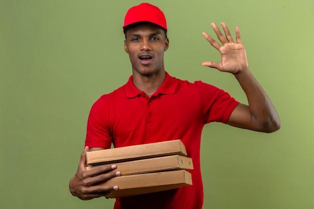 Il giovane fattorino afroamericano che indossa la camicia e il cappuccio di polo rossi che stanno con la pila di scatole della pizza che fanno il saluto gesturing sopra il verde isolato