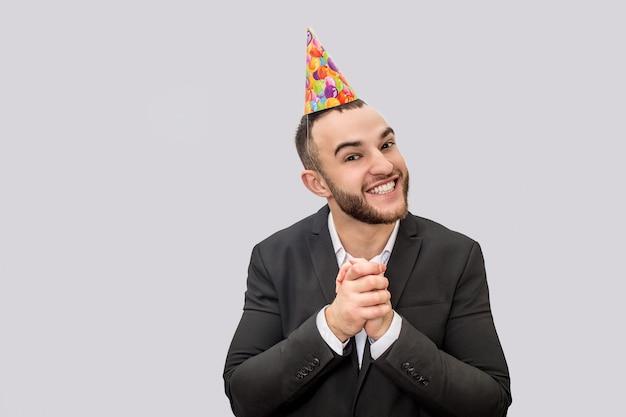 Il giovane felice ed emozionante tiene insieme le mani. guarda la telecamera e sorride. il ragazzo indossa un cono festivo sulla testa.
