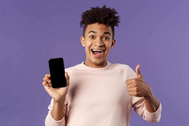 Il giovane felice, il ragazzo ispanico con i dreadlocks consiglia l'app, il servizio di consegna online o l'ordine di cibo, mostra il pollice in su, sorride eccitato, tiene il cellulare, mostra lo schermo dello smartphone
