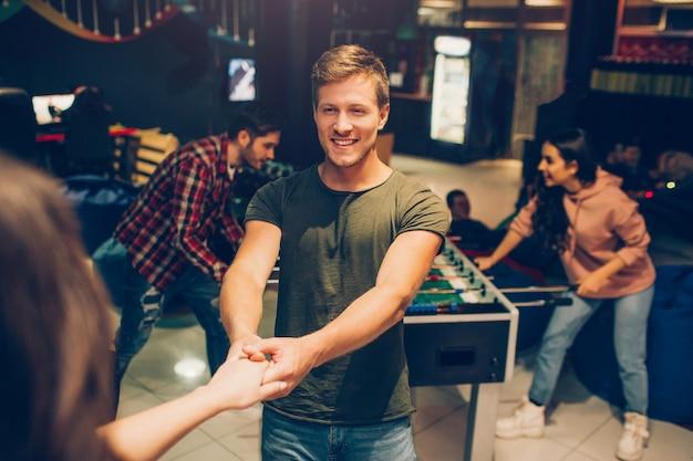 Il giovane felice tiene la mano della donna e la guarda. lui sorride. le persone stanno nella sala da gioco. i loro amici giocano a calcio balilla dietro.