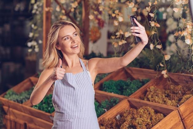 Il giovane fiorista femminile sorridente che prende il selfie sul telefono cellulare che mostra il pollice su firma dentro il negozio