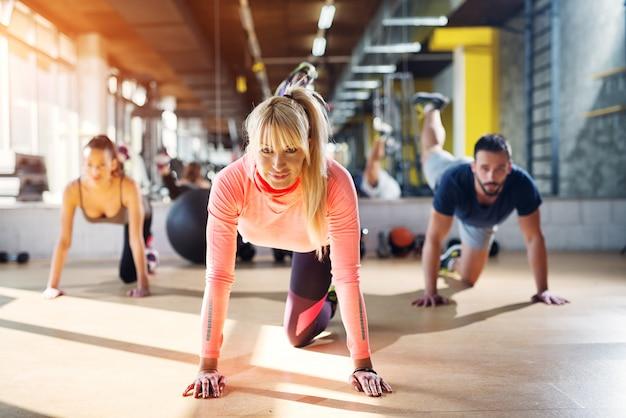 Il giovane forte istruttore femminile della palestra che mostra un certo equilibrio del corpo risolve.