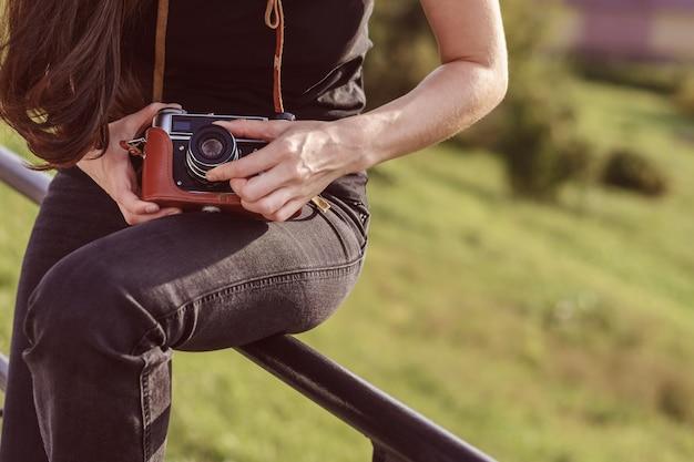 Il giovane fotografo femminile felice cammina nel parco con la retro macchina fotografica