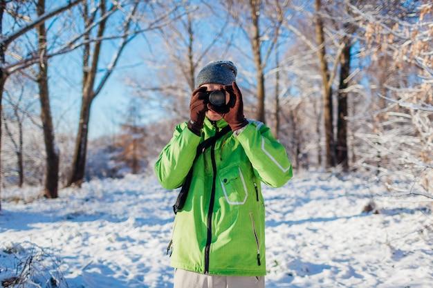 Il giovane fotografo scatta foto della foresta invernale usando la fotocamera. giovane che spara le foto all'aperto